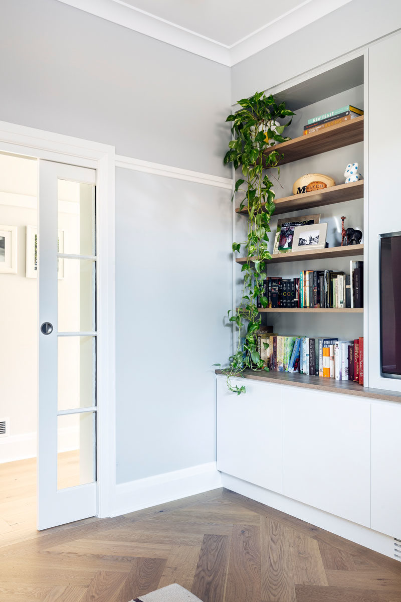 Home Library Ideas - This modern home library has a glass pocket door, while inside, open wood shelving provides a place to show off books and decor, while cabinets below provide additional storage. #HomeLibrary #Playroom #Shelving