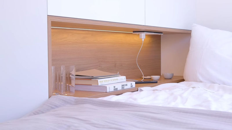 Small Apartment Ideas - Beside this modern bed, there's a built-in wood lined shelf that provides a place for charging a phone, and has hidden bedside light. #BedroomShelf #BedroomDesign #SmallApartmentIdeas