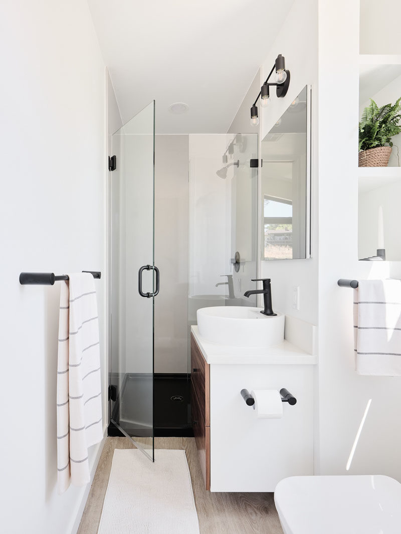Tiny House Ideas - In the ensuite bathroom of this tiny house, a glass shower door allows light to travel through to the shower, while beside the toilet are built-in shelves. #TinyHouseIdeas #TinyHouseBathroom #ModernBathroom #SmallBathroom #BathroomDesign