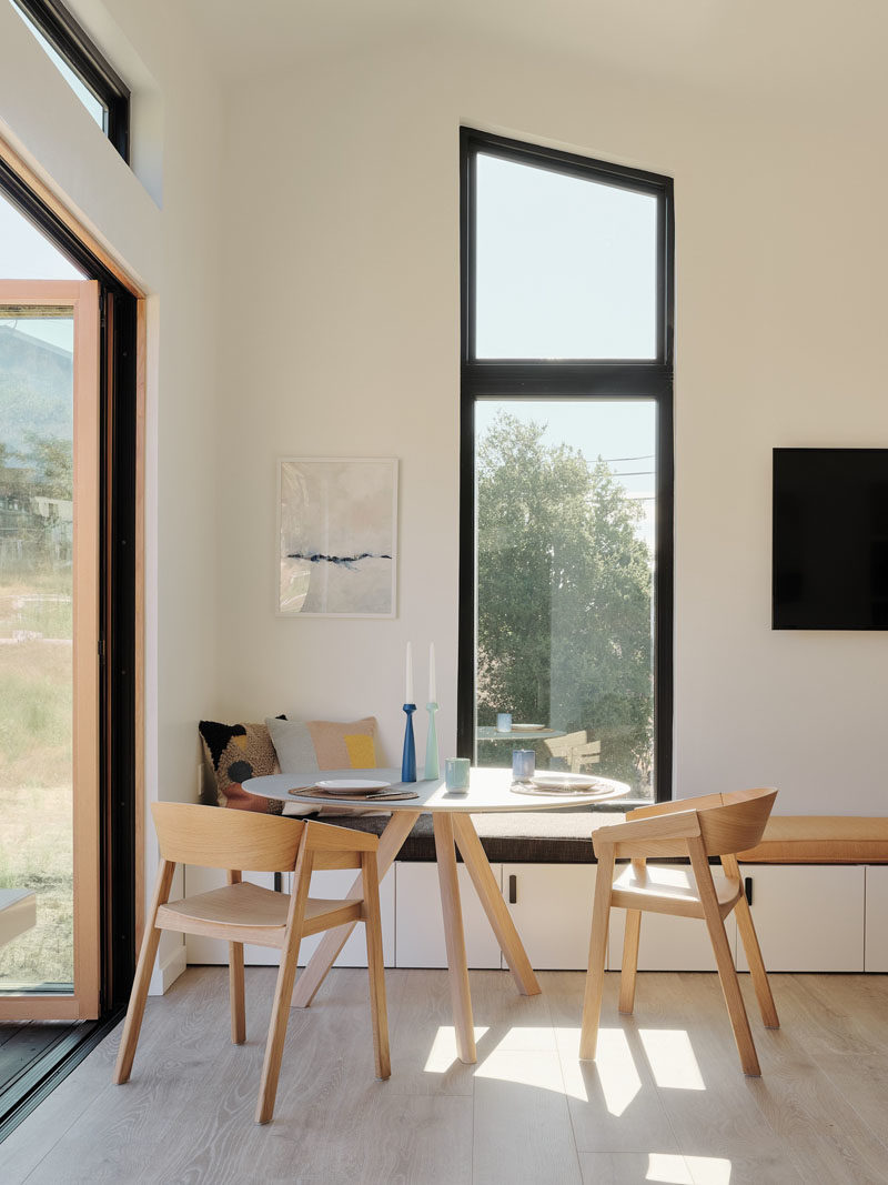 Tiny House Ideas - This modern tiny house has a 3 panel folding door that connects the interior to the outdoor space, while just inside the door is a small dining area with a bench that runs the length of the wall. #TinyHouseIdeas #ModernTinyHouse #TinyHouseDining #TinyHouseSeating