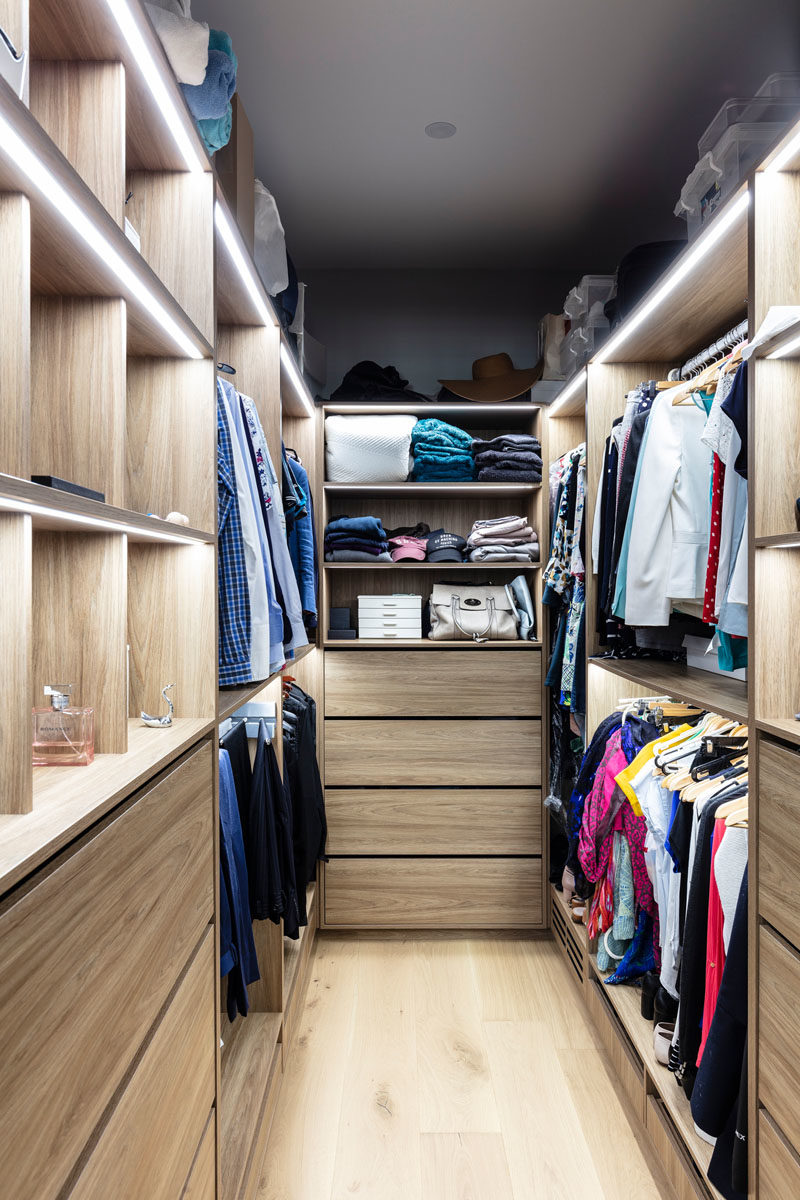 Walk-In Closet Ideas - This modern his and hers walk-in closet has plenty of room for hanging and storing clothes, while strips of LED lighting provide ample light. #WalkInCloset #ClosetIdeas