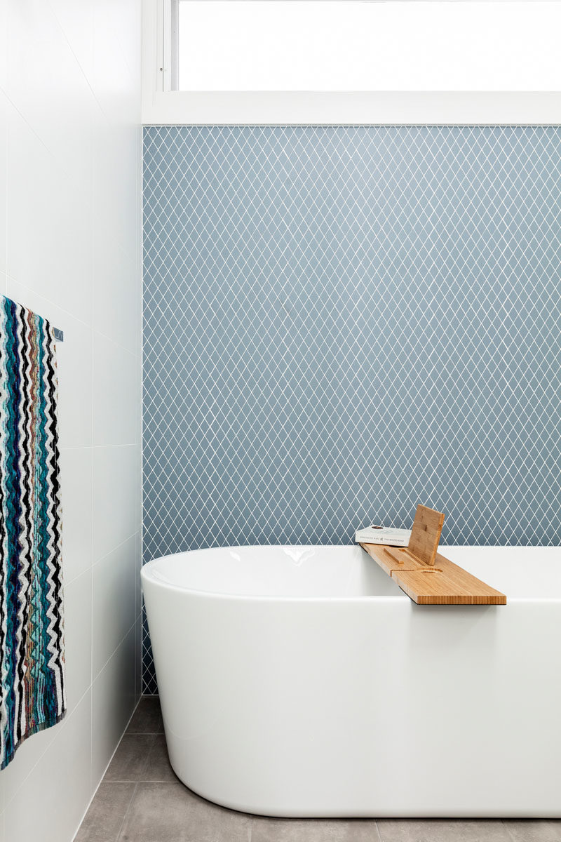 Bathroom Ideas - Blue-grey tiles have been used to create an accent wall in this modern bathroom with a freestanding bathtub. #ModernBathroom #BathroomIdeas #TileAccentWall
