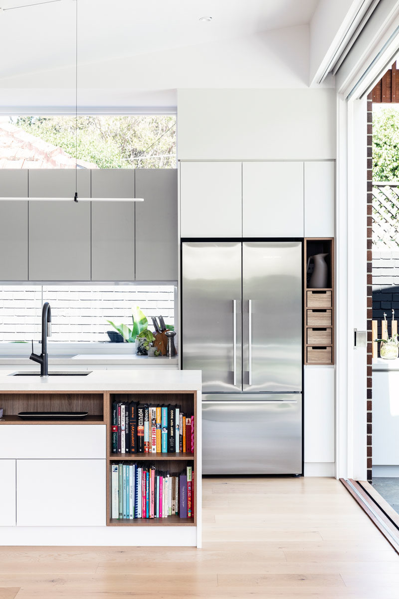 Kitchen Ideas - In this modern kitchen, minimalist white cabinets sit flush with the walls, while the island provides additional counter space and open shelving for recipe books. #KitchenIdeas #ModernKitchen #KitchenDesign #KitchenIsland