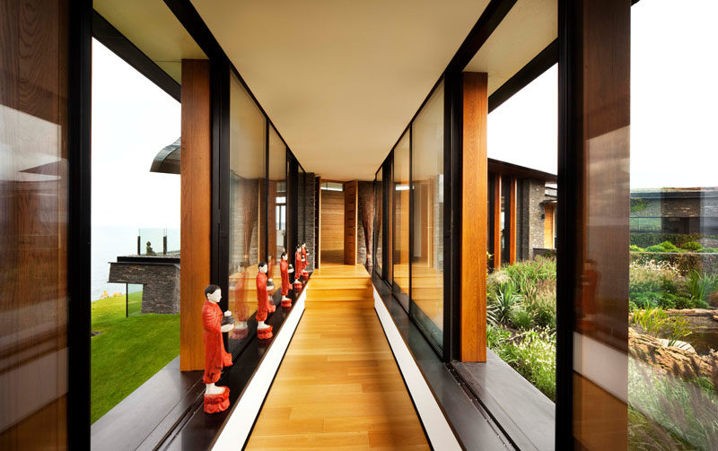 Hallway Ideas - A window-lined hallway connects the various areas of this modern house, and showcases the wood flooring, and the views on either side. #Hallway #Windows