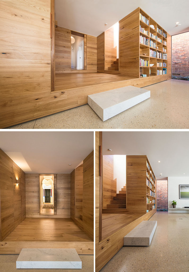 This wood lined foyer separates the old part of the house from the new modern addition. A small step down leads to an open plan kitchen and living room, where a built-in bookshelf creates a small library area. #Foyer #Stairs #Bookshelf