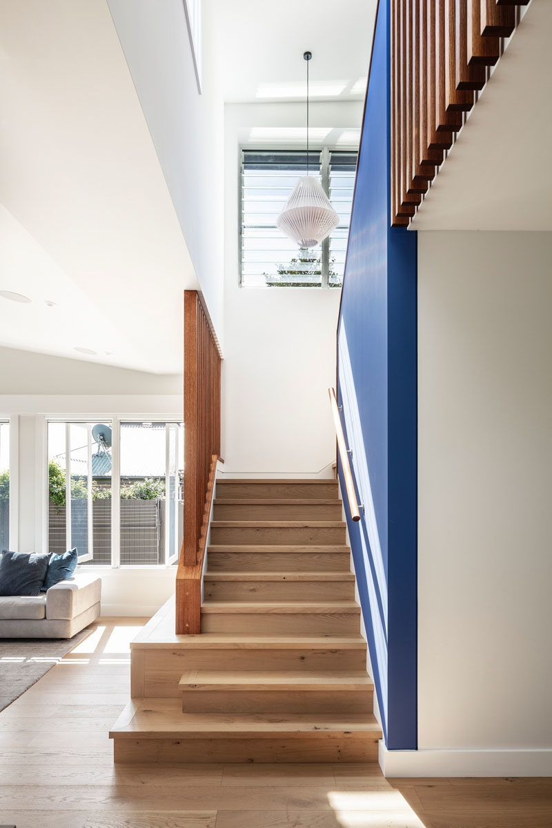 Stair Ideas - This updated house has a blue accent wall that follows the wood stairs. #BlueAccentWall #WoodStairs