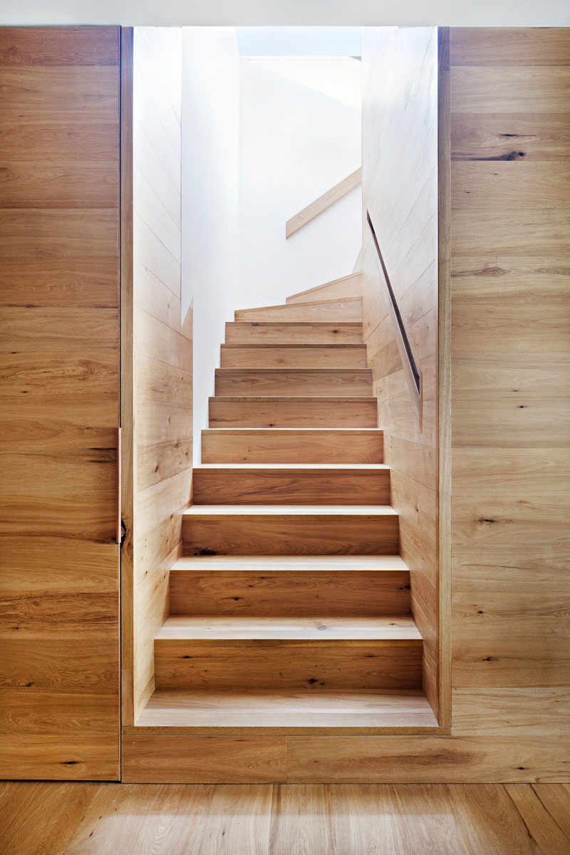 Stair Ideas - This modern house has oak wood stairs with a built-in handrail that lead to the upper floor of the home. #Stairs #WoodStairs #ModernHouse