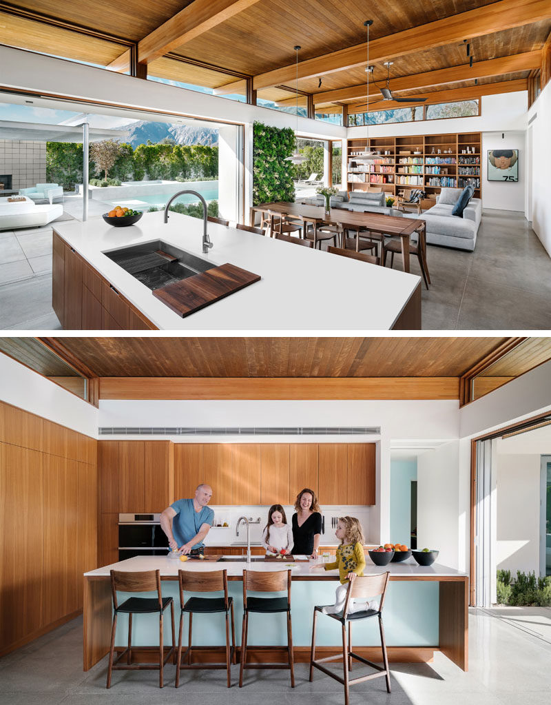 Kitchen Ideas - In this modern kitchen, minimalist wood cabinets have been made from reconstituted poplar, that's been dyed to resemble an engineered teak. These cabinets add warmth to the space, and contrast the white surfaces, backsplash, and storage accessories from Corian. #ModernKitchen #WoodKitchen #ModernKitchenDesign #KitchenIdeas
