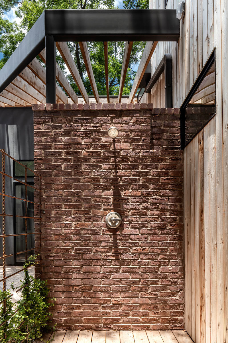 Bathroom Ideas - This modern house has an outdoor shower attached to a brick wall, that's tucked away in the backyard. #OutdoorShower #BathroomIdeas