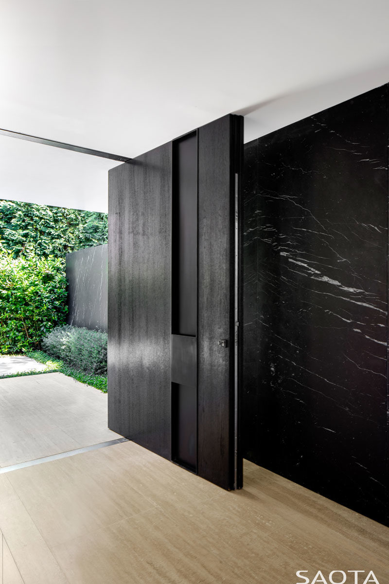 Front Door Ideas - This modern house has a large oversized black pivoting front door that opens to reveal the interior of the home, which was conceived as a gallery-like space. #FrontDoor #PivotingDoor #FrontDoorIdeas #BlackFrontDoor #PivotDoor