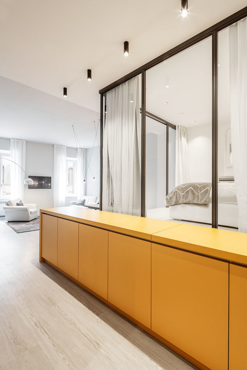 Small Apartment Ideas - Upon entering this small apartment, there's a long yellow sideboard that greets visitors, however the top of the sideboard can be lifted to reveal the kitchen counter, that has a sink and a cook top, with the 'lid' also acting as a backsplash. #SmallApartment #SmallApartmentIdeas #HiddenKitchen #KitchenIdeas
