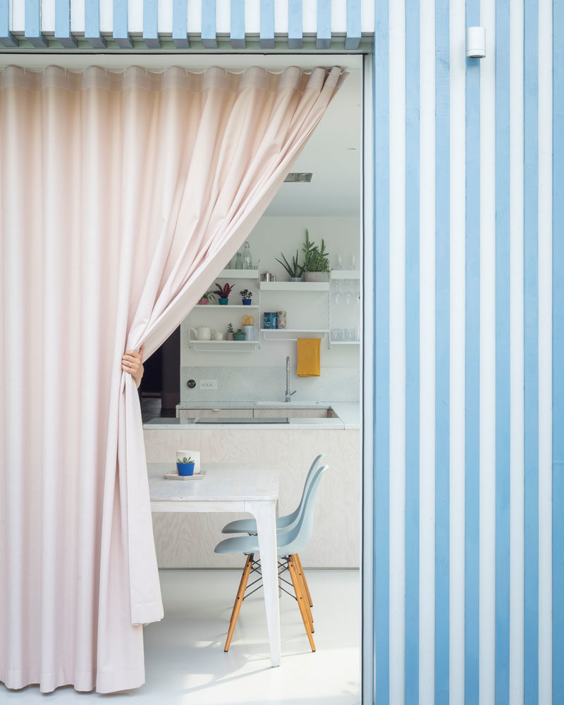 Facade Ideas - The bright blue and white striped facade is softened by a  full wall pink curtain, bringing interest to the space and providing privacy when needed. #Facade #StripedFacade #ModernArchitecture