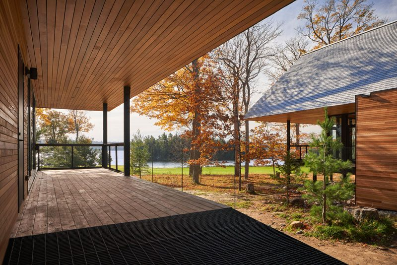 This collection of modern cabins are clad in shiplapped wood, which adjoins a glass pavilion that holds an open-plan living and dining space. They also have a deep hip roof that's clad with cedar shingles. #ModernCabin #Architecture #CabinDesign