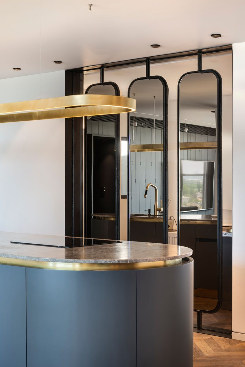 Separating the kitchen from the home office in this modern apartment, is a collection of three steel and mirror partitions. Each individual partition turns on an axis and can be adjusted to any chosen angle, while the mirrors reflect light throughout the interior. #PartitionIdeas #WallPartition #InteriorDesign #MirroredPartition