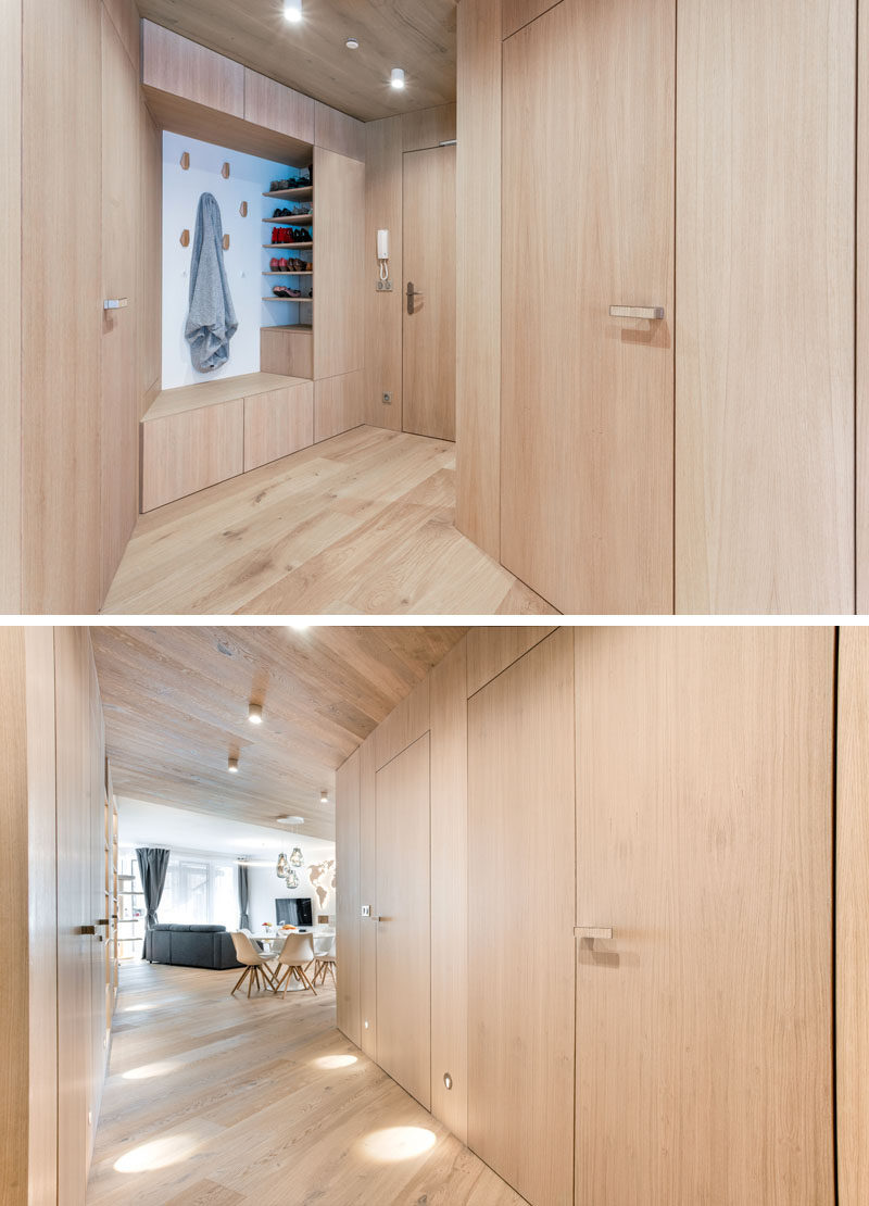 Entryway Ideas - In the entryway of this modern apartment, a custom nook has wall hooks, open shelving, and a cabinet that doubles as a bench. #EntrywayIdeas #InteriorDesignIdeas #ApartmentIdeas #