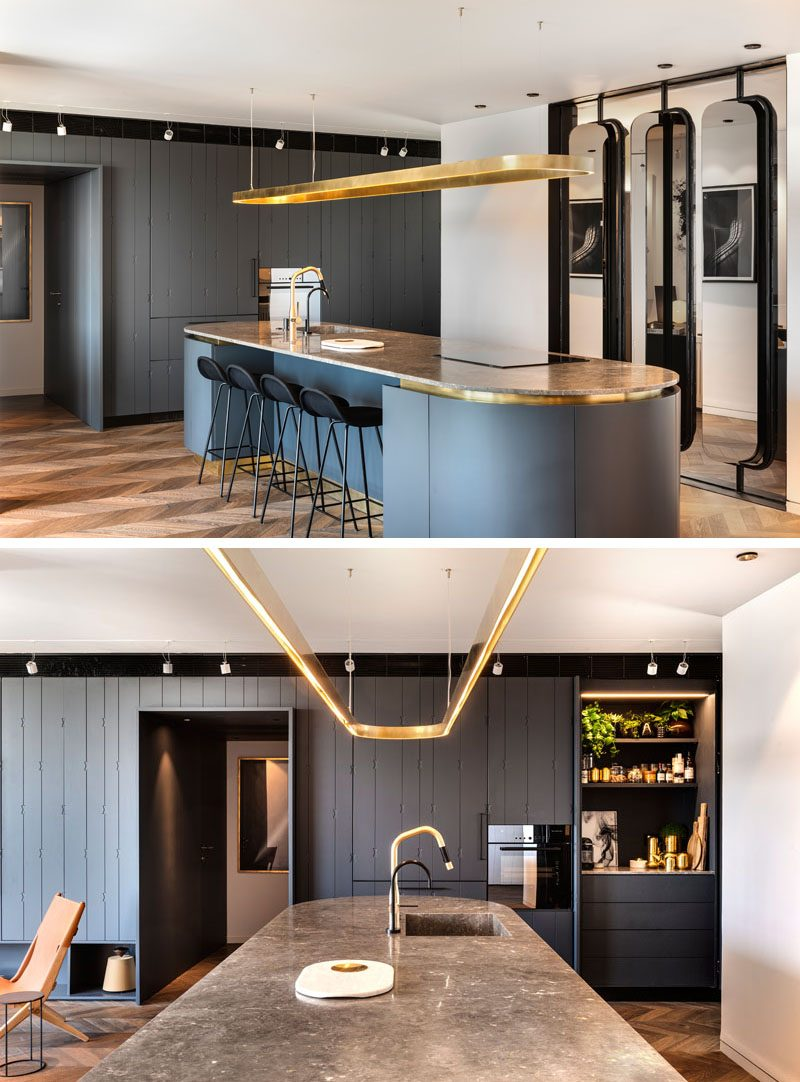 In this modern kitchen, there's a spacious island that's been designed with an oval shape. It includes touches of brass and is clad in curving cupboards that are made from wood and painted in a coal-grey with a blue tinted pigment. The island countertop is brown marble with light colored veins, and the light fitting above the island is also brass, pressed into an oval shape. #ModernKitchen #OvalIsland #KitchenIslandIdeas #KitchenIdeas #KitchenDesign