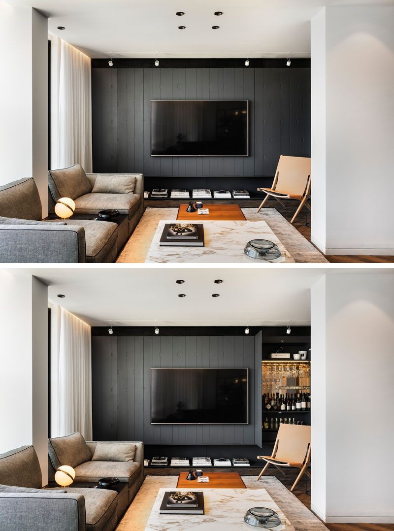In this modern living room, there's a grey wall that runs the width of the apartment, and has hidden design features, like a bar with a mirrored wall and stemware storage. #LivingRoomIdeas #ModernLivingRoom #HiddenBar