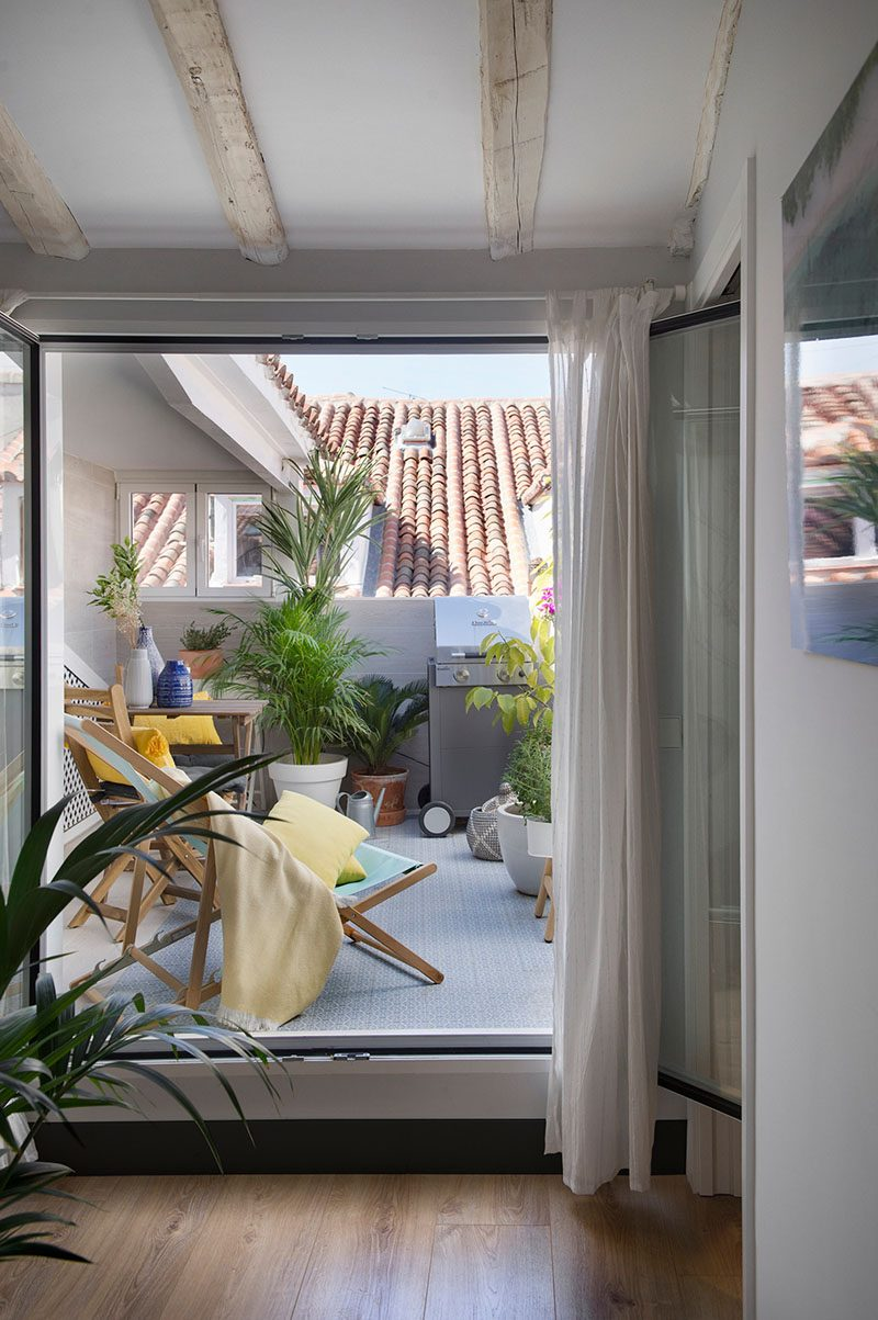 Just inside this contemporary apartment and by the front door, is a small terrace area that's furnished with some seating, a place to eat, and a bbq. #TerraceIdeas #BalconyIdeas #OutdoorSpace
