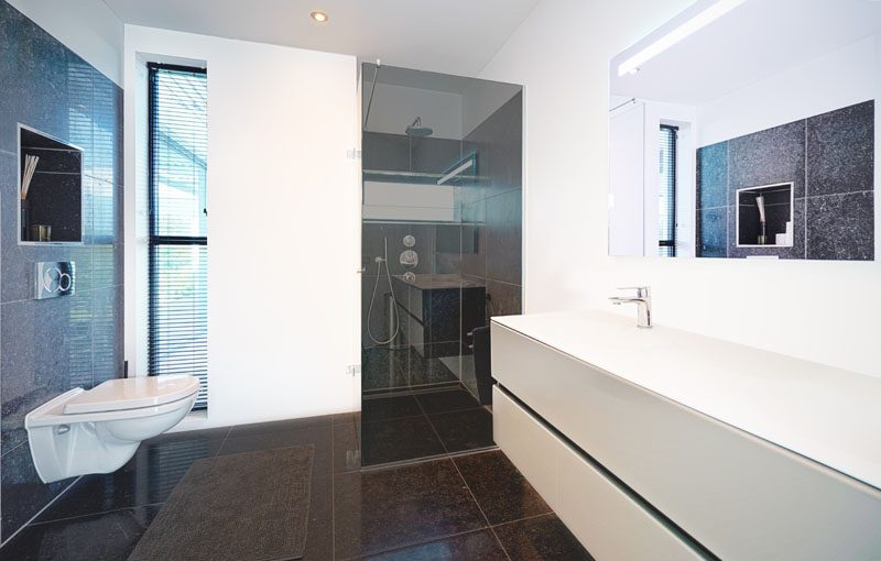 In this modern bathroom, a niche has been built into the wall above the toilet, while dark glass frames the shower, and a floating white vanity sits below a large mirror. #ModernBathroom #BathroomNiche #FloatingVanity #DarkGlass