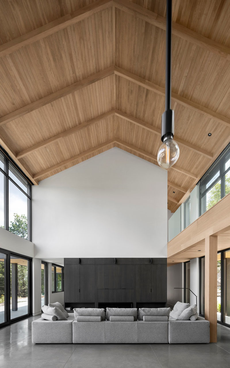 Modern Barnhouse Ideas - Inside this modern barnhouse, the gabled roof is highlighted by the wood-line ceiling that draws the eye upward. In the living room, a collection of cabinets houses the television and fireplace. #ModernBarnhouse #GabledRoof #ModernArchitecture #WoodCeiling