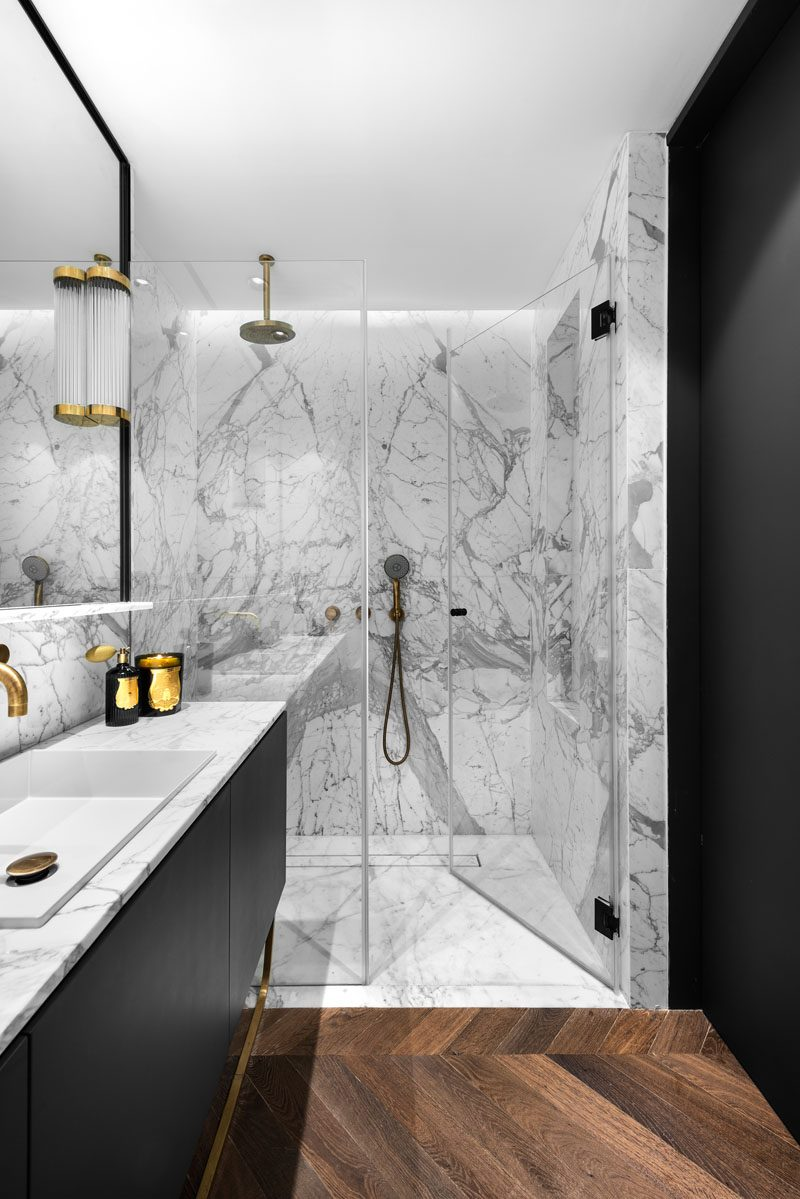 In this modern grey and black bathroom, a glass enclosed shower has hidden lighting that creates a soft glow for the space. #ModernBathroom #BathroomDesign #ShowerDesign