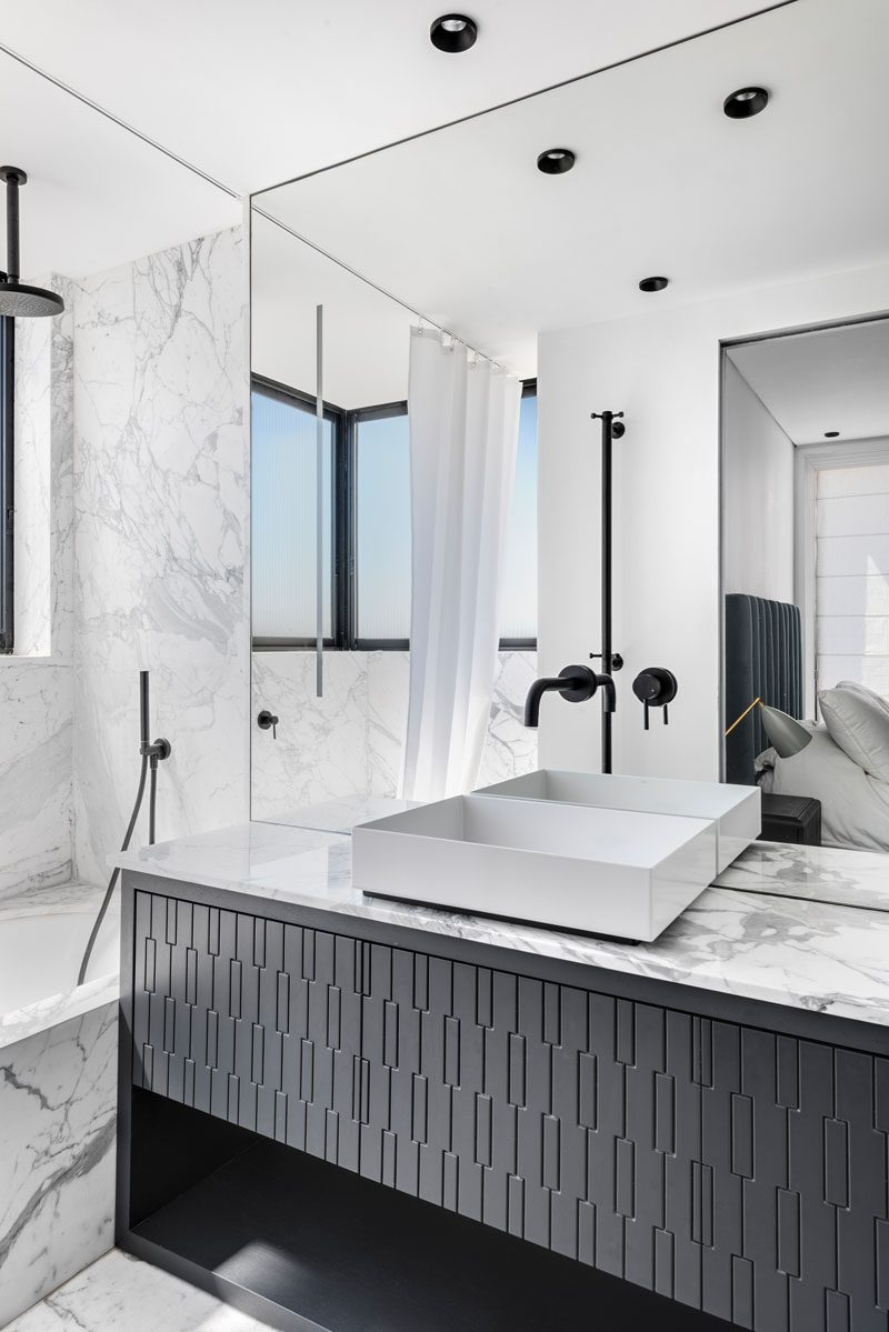In this modern bathroom, grey stone walls and countertops are contrasted by black accents and a black vanity. #ModernBathroom #BlackAndGreyBathroom #BathroomIdeas