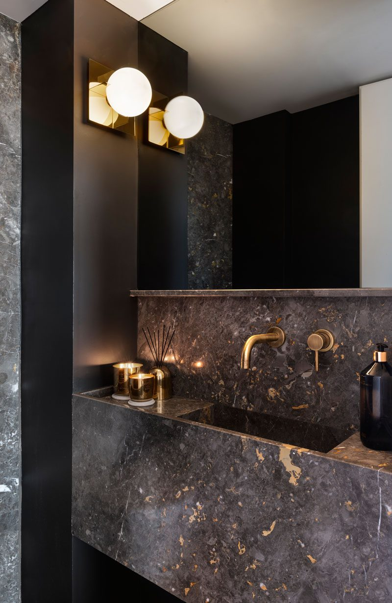 In this modern powder room, metallic accents have been paired with dark stone and black walls for a bold and dramatic appearance. #ModernPowderRoom #BathroomDesign