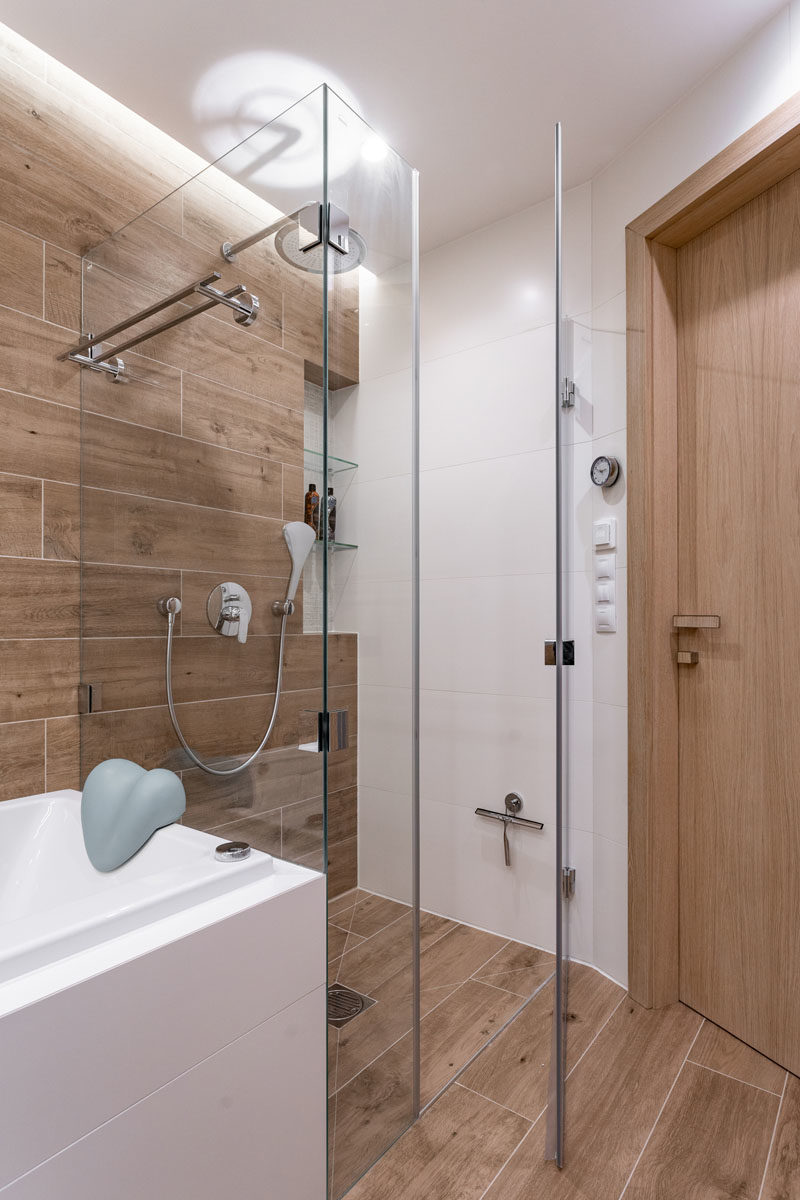 Bathroom Ideas - In the bathroom, tiles with a wood grain finish cover the wall and floor, while the glass shower surround allows light to travel throughout the small space, making it feel larger and brighter. #ModernBathroom #WoodTiles #BathroomIdeas #BathroomDesign