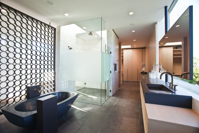 Bathroom Ideas - This modern master bathroom features a glass enclosed shower that receives natural light from the skylights above, while a black freestanding bathtub matches the vanity countertop with integrated sinks. #MasterBathroom #BathroomIdeas #FreestandingBathtub #BathroomVanityIdeas