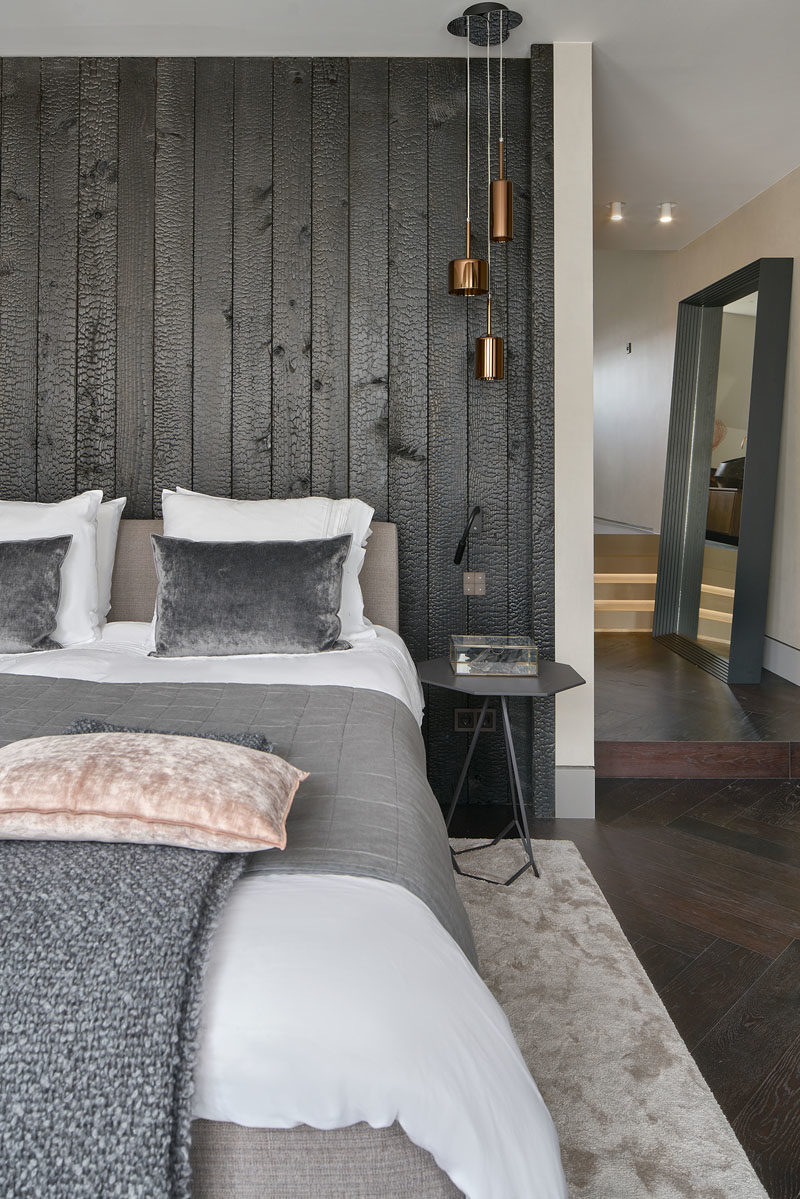 Bedroom Ideas - In this modern  master bedroom, a burnt wood (shou sugi ban) accent wall creates a bold statement in the room. #BedroomIdeas #AccentWall #BurntWoodWall #ShouSugiBan