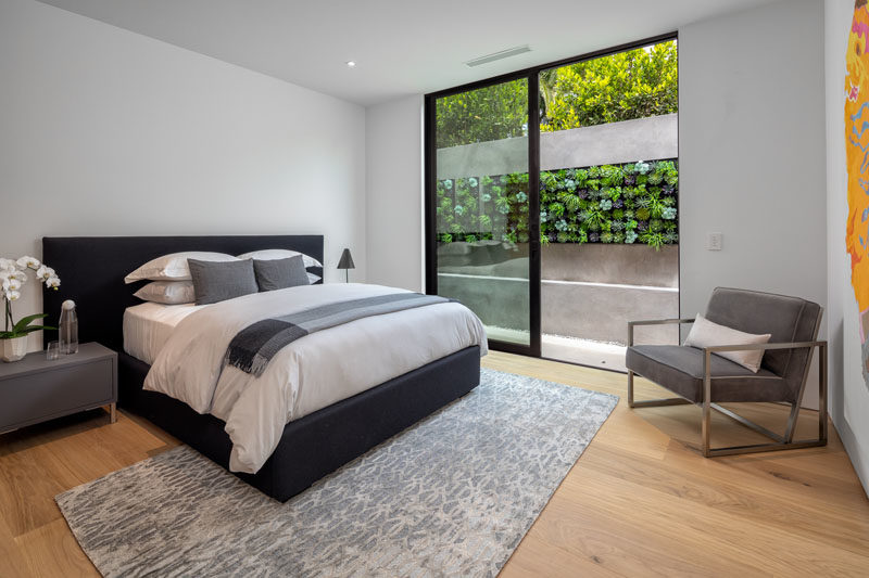 Bedroom Ideas - In this modern guest bedroom, a sliding glass door opens to a small outdoor space with a succulent wall. #GuestBedroom #BedroomIdeas #SucculentWall