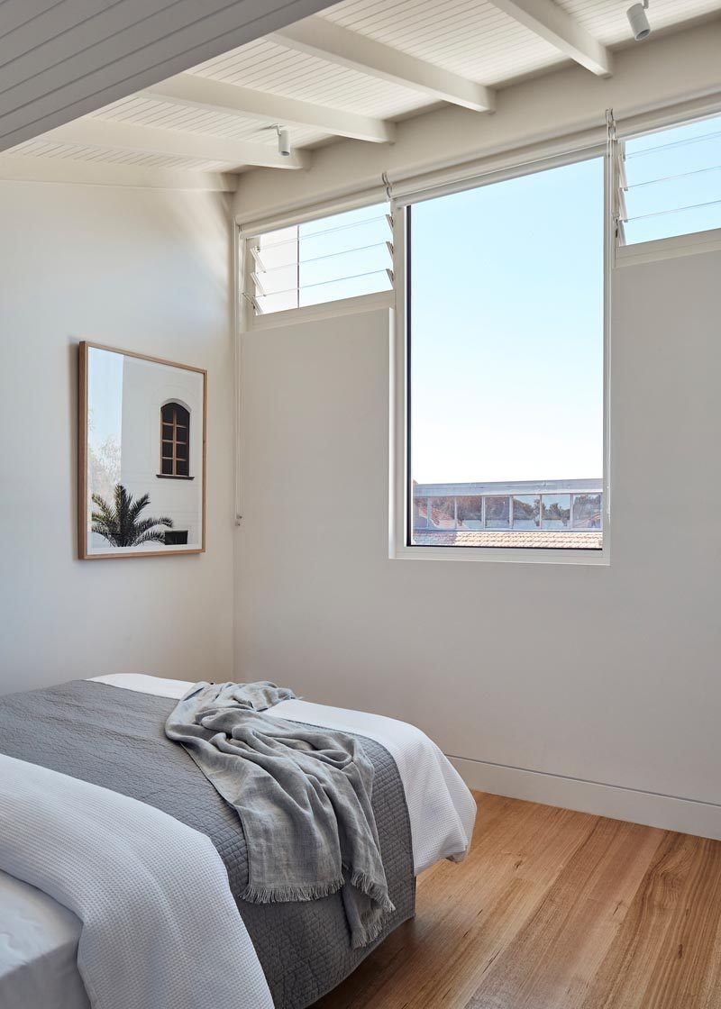 This modern bedroom has a single large window with views of the neighborhood, and is flanked by smaller louver windows, that help with air flow. #Windows #ModernWindows #Bedroom #BedroomDesign