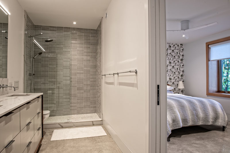 Bathroom Ideas - A pocket door opens to reveal the en-suite bathroom, where there's a walk-in shower and a vanity with double sinks. #BathroomIdeas #ModernBathroom