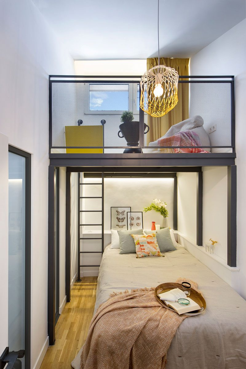 This modern and small bedroom has a loft that's accessed via a small black ladder. #SmallBedroom #BedroomLoft #BedroomDesign