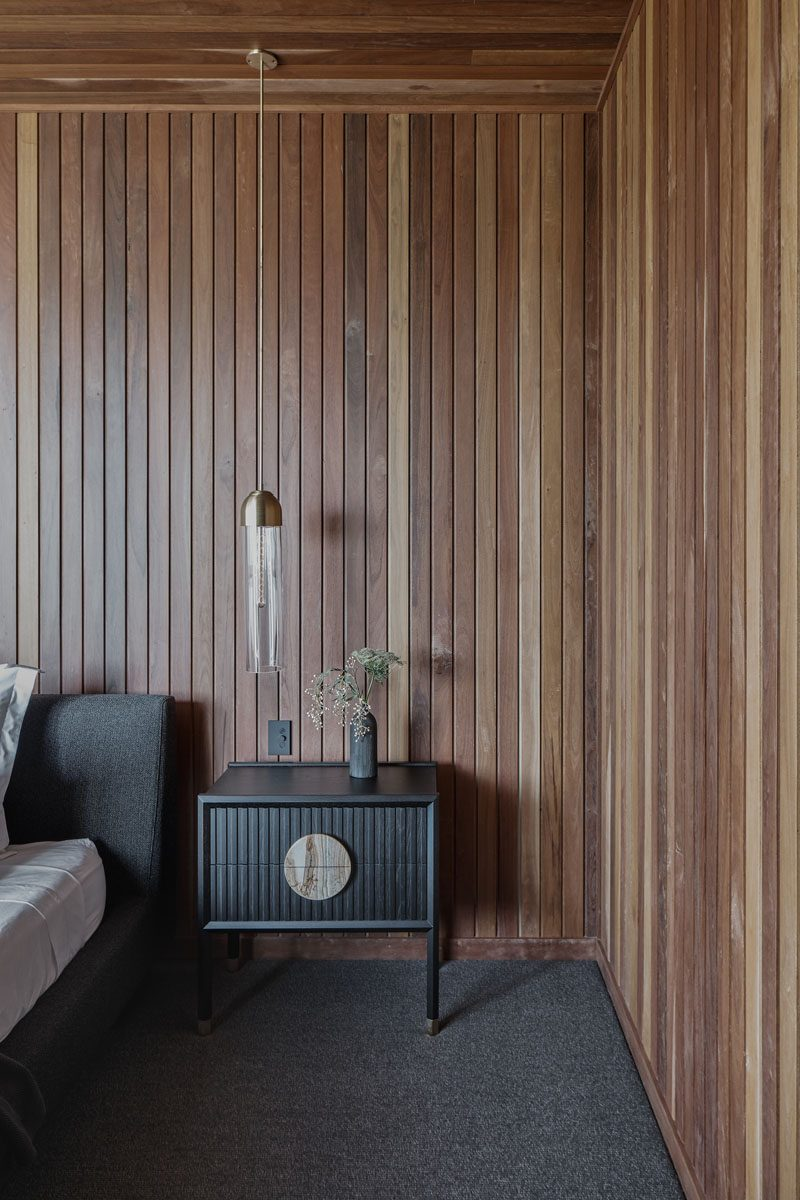 Thin lengths of wood in different shades have been used on the walls and ceiling, creating a natural warmth for this modern bedroom. #BedroomDesign #WoodWalls #WoodCeiling #ModernBedroom