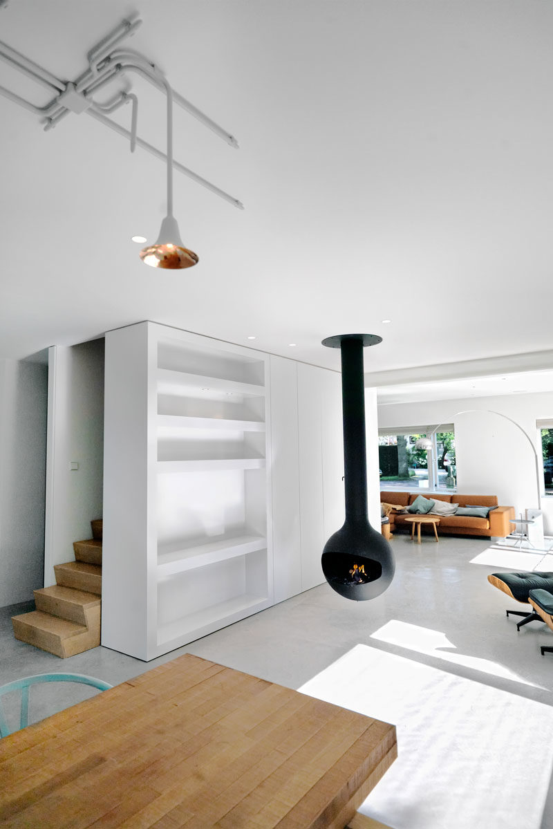 Interior Design Ideas - Concrete floors have been added throughout this new house addtiion, while a hanging black fireplace provides contrast to the bright white interior, and a new staircase acts as the backbone of the house, connecting the first floor and attic to the ground level and garden. #HangingFireplace #WhiteInterior