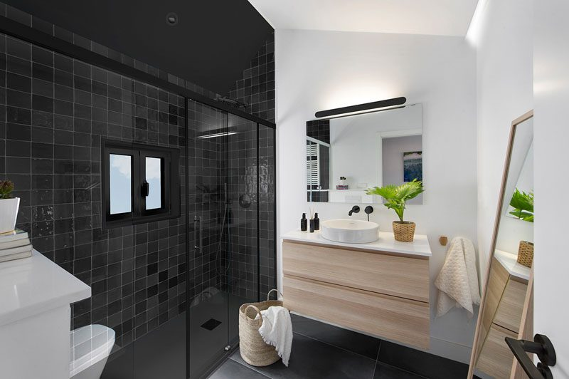 In this modern bathroom, square black tiles define the shower and allow the window frame to blend in, while a light wood vanity adds a natural touch to the room. #ModernBathroom #BlackShower #BlackTiles #BathroomIdeas #WoodVanity