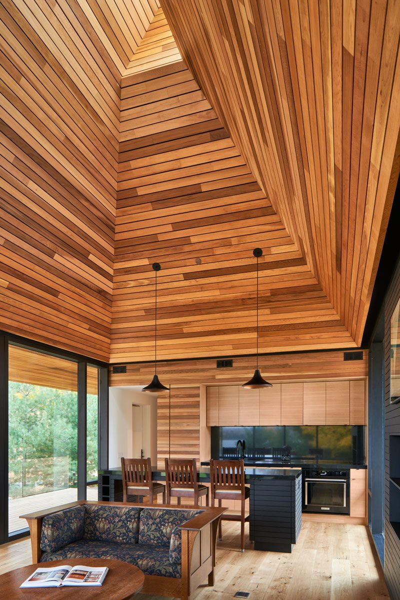 This modern cabin has an open living room and kitchen that are naturally lit from above via a periscope window in the gable. #ModernCabin #WoodCeiling #PeriscopeWindow #LivingRoom #CabinInterior