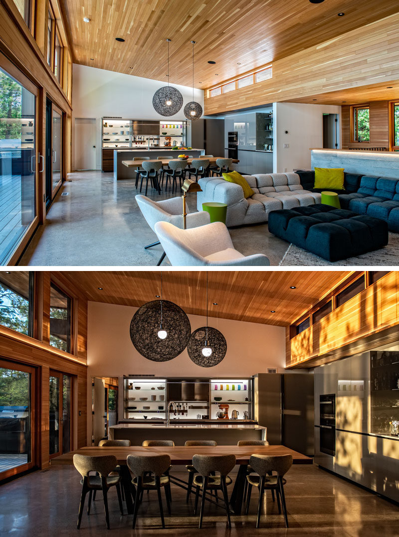 Dining Room Ideas - The dining area of this modern cottage separates the living room from the kitchen, with the large dining table making it easy to host family diners. The dining table has also been positioned in a way that no one has their back to the view. #DiningRoom #ModernCottage #WoodCeiling