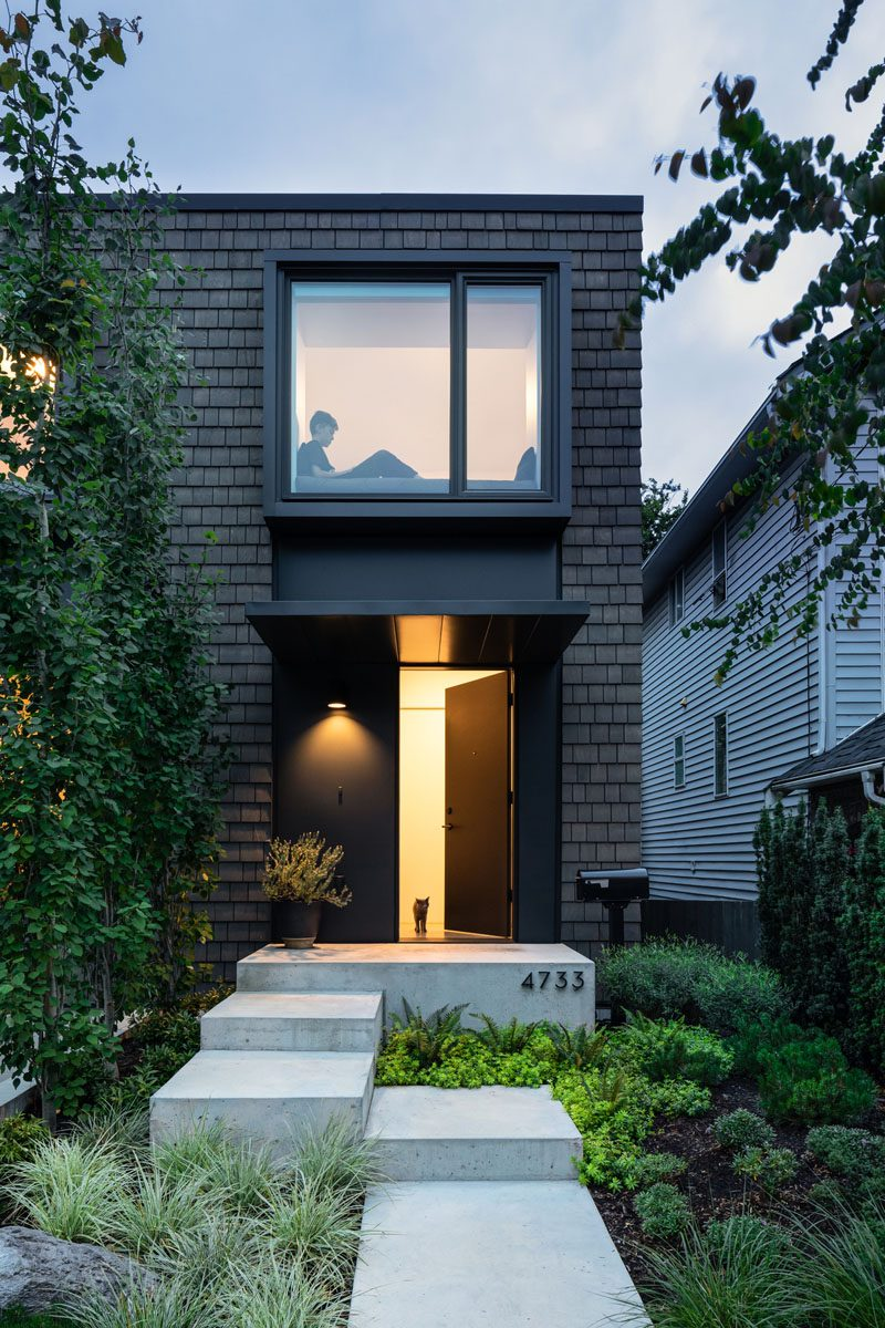 The path to the front door of this modern house runs alongside a line of trees that creates a barrier from the sloped driveway, and provides a view of one of the two bay windows on the second floor of the house. #ModernHouse #ModernBayWindow #DarkShingles #ModernLandscaping #Path