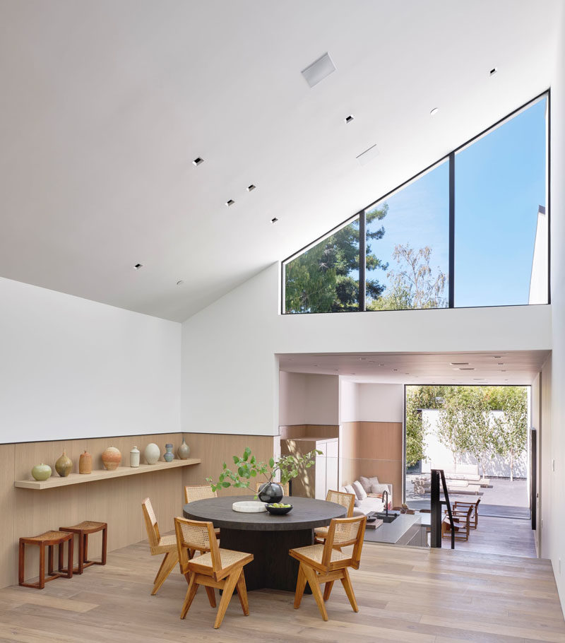 The social areas of this modern house are split between the living room and dining area, with the kitchen located on a lower level. #ModernHouse #DiningRoom #Windows