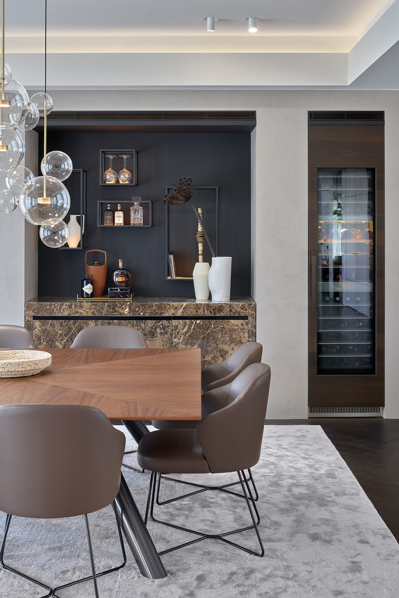 Dining Room Ideas - This modern dining room has a recessed home bar and a separate built-in wine fridge. #DiningRoomIdeas #ModernHomeBar #BuiltInBar #BuiltInWineFridge #WineStorage