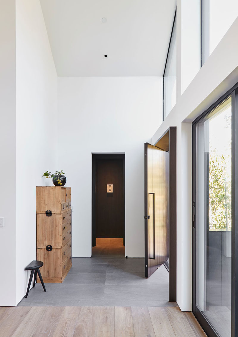 Inside the pivoting front door of this modern house, is a foyer with high ceilings and grey tiles. #ModernHouse #ModernInterior #Foyer