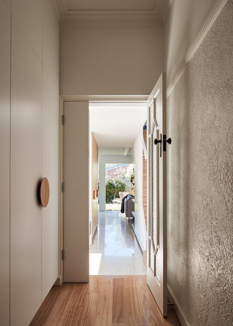 This hallway connects a new and modern extension with the original house. Opposite the front door are stairs that lead to a new second floor of the extension. #ModernHallway