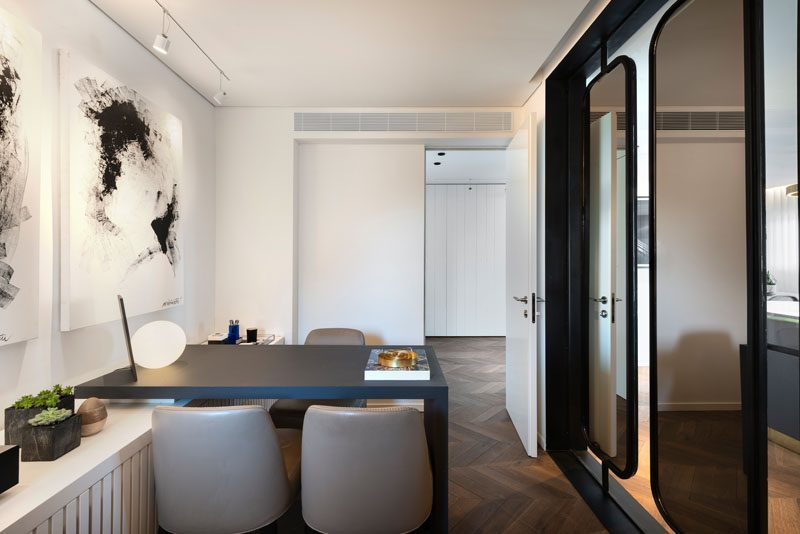 In this modern home office, there's white cabinetry that runs the length of the room, while a black desk complements the black-framed mirrored partitions and the abstract wall art. #ModernHomeOffice #HomeOfficeIdeas #MirroredPartition