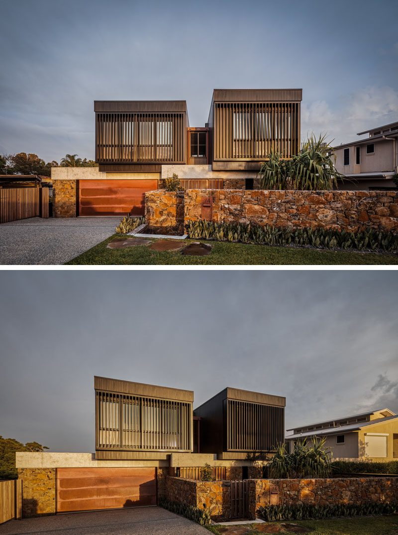 At the front of this modern house are two boxes that sit atop the ground level, and have louvres for privacy, security, and ventilation. #ModernHouse #HouseDesign #StoneWall #ModernArchitecture #Louvres
