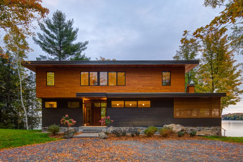 This new home was designed to take full advantage of the lake views and the landscaped spaces that surround it. Natural stone anchors the base of the cottage while dark grey and natural wood siding give the exterior a modern feel. #ModernHouse #Stone #Architecture #GreySiding #WoodSiding