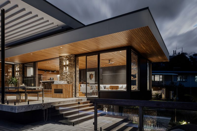 Sliding doors open the interior social spaces of this modern house, to a covered patio with steps that lead down to the backyard. #CoveredPatio #ModernHouse #WoodCeiling