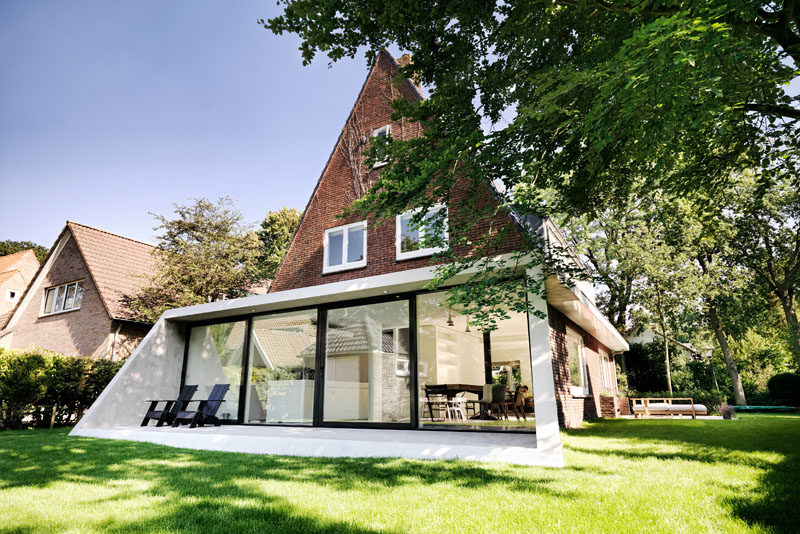 Architecture Ideas - This brick house received a new angled addition, that enlarged it with an open floor plan, added a view to the garden, and continues the slope of the original roof. #ModernArchitecture #HouseAddition #GlassWall