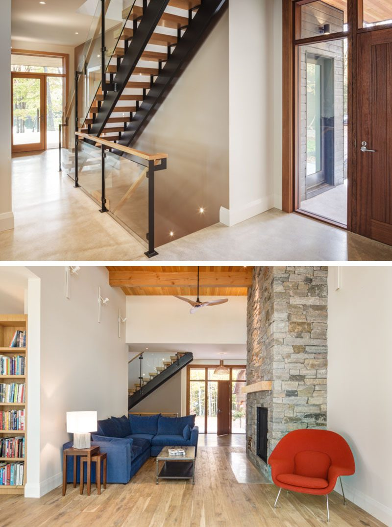 This modern lakeside house has a front door surrounded by windows on three sides, that leads into a cozy living room with seating around a wood burning fireplace. #FrontDoor #ModernStairs #InteriorDesign #LivingRoom #Fireplace.